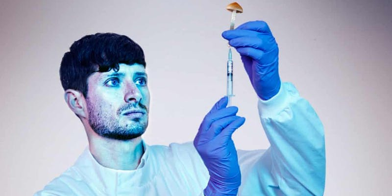 Photo; Scientist wearing protective lab clothing injecting a mushroom