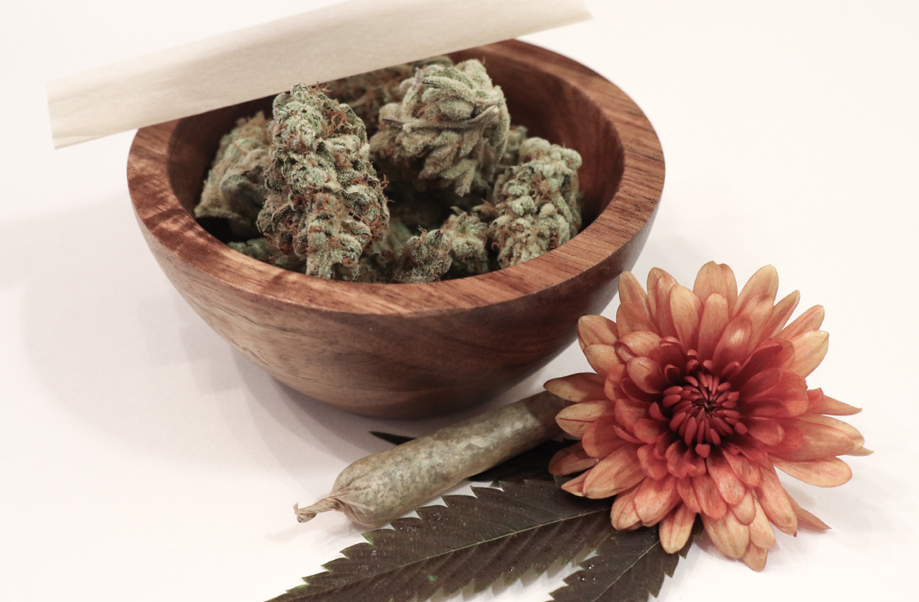 Photo; close up cannabis in wooden bowl, rolled marijuana cigarette, pink chrysanthemum and cannabis lead decoration